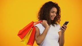 Афро-американская женщина держа хозяйственные сумки и смартфон, онлайн приобретение сток-видео