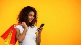Афро-американская женщина держа хозяйственные сумки и смартфон, онлайн приобретение стоковые фото