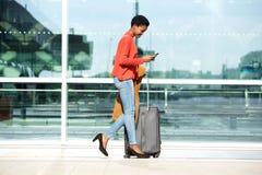 Афро-американская женщина идя с чемоданом и мобильным телефоном стоковые изображения rf