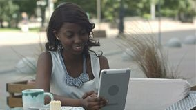 Афро-американская женщина имеет видео- конференцию на ее планшете сидя во внешнем кафе сток-видео