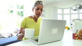 Афро-американская женщина используя компьтер-книжку в кухне дома акции видеоматериалы