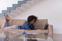 Афро-американская женщина используя компьтер-книжку на софе Стоковое фото RF