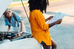 Афро-американская женщина ища назначение на карте пока проверять друга стоковые изображения rf