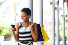 Афро-американская женщина идя с мобильным телефоном и хозяйственными сумками Стоковое Изображение RF