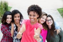 Афро-американская женщина показывая большой палец руки с группой в составе подруги Стоковые Изображения RF
