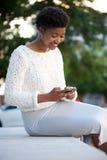 Афро-американская женщина посылая текстовое сообщение с мобильным телефоном стоковая фотография rf
