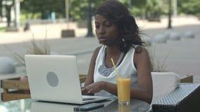 Афро-американская женщина работая на juce компьтер-книжки внешнем и выпивая видеоматериал