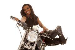 Афро-американская женщина сидит на ногах мотоцикла вверх смотря стоковая фотография rf