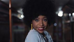 Афро-американская женщина смотря камеру и усмехаясь положение в общественном транспорте, steadicam сняла : сток-видео