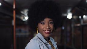 Афро-американская женщина смотря камеру и усмехаясь положение в общественном транспорте, steadicam сняла Она держа акции видеоматериалы