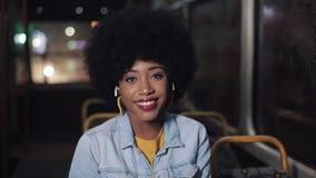 Афро-американская женщина смотря камеру и усмехаясь усаживание в общественном транспорте, steadicam сняла : e сток-видео