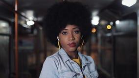 Афро-американская женщина смотря положение камеры в общественном транспорте, steadicam сняла : Света города сток-видео