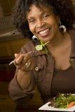 Афро-американская женщина усмехаясь ел салат Стоковые Фотографии RF