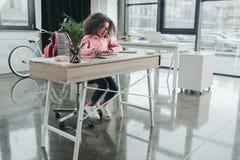 Афро-американская коммерсантка девушки при вьющиеся волосы работая в современном офисе Стоковое Изображение RF