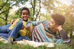 Афро-американская маленькая девочка в парке с отцом лежа d Стоковое Изображение RF