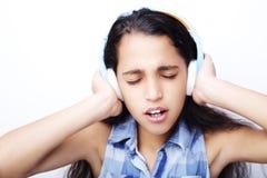 Афро-американская маленькая девочка с наушниками слушая к музыке стоковые изображения