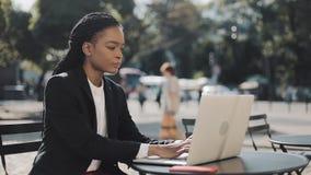 Афро-американская молодая женщина работая на усаживании ноутбука сидя в кафе на летней террасе Дело, работая видеоматериал