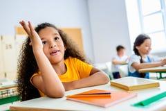 Афро-американская рука повышения школьницы для того чтобы ответить вопрос об учителей стоковое изображение