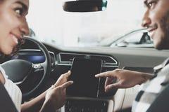Афро-американская семья на автосалоне Мать и отец используют таблетку в новом автомобиле Стоковое Изображение RF