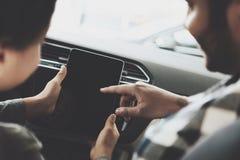 Афро-американская семья на автосалоне Отец и сын используют таблетку в новом автомобиле Стоковые Фотографии RF
