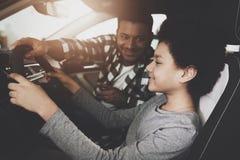 Афро-американская семья на автосалоне Отец и сын пробуют вне новый автомобиль стоковая фотография rf