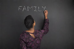 Афро-американская семья сочинительства учителя женщины на предпосылке доски черноты мела стоковые изображения