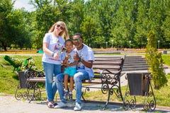 Афро-американская счастливая семья: черные отец, мама и ребёнок на природе Используйте его для принципиальной схемы ребенка, pare стоковое изображение