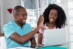 Афро-американские пары делая онлайн ресервирование с компьтер-книжкой стоковые фото