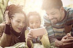 Афро-американские родители с их дочерью в парке используя mobil стоковое фото rf