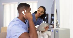 Афро-американские специалисты работая совместно в рабочей станции больницы Стоковое фото RF