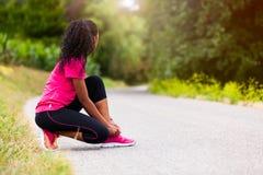 Афро-американский бегун женщины затягивая шнурок ботинка - фитнес, pe Стоковое Изображение RF
