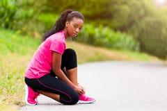 Афро-американский бегун женщины затягивая шнурок ботинка - фитнес, pe Стоковые Изображения RF