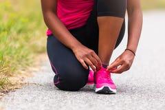 Афро-американский бегун женщины затягивая шнурок ботинка - фитнес, pe Стоковые Фотографии RF