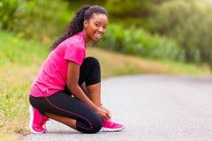 Афро-американский бегун женщины затягивая шнурок ботинка - фитнес, pe Стоковые Изображения