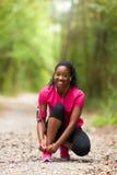 Афро-американский бегун женщины затягивая шнурок ботинка - фитнес, pe Стоковое Фото