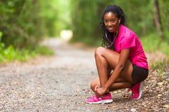 Афро-американский бегун женщины затягивая шнурок ботинка - фитнес, pe Стоковое Изображение