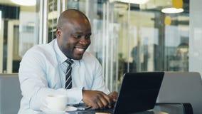 Афро-американский бизнесмен в официально носке имея онлайн видео- звонок с его компьтер-книжкой и говоря к его семье до конца акции видеоматериалы