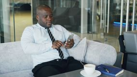Афро-американский бизнесмен в официально одеждах печатая sms на его smartphone в современном кафе во время перерыв на ланч Он смо сток-видео