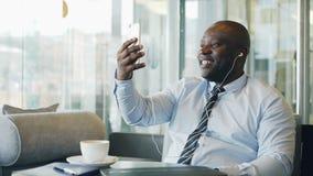 Афро-американский бизнесмен в официально одеждах смеясь над и говоря к его семье через болтовню smartphone видео- в воздушном акции видеоматериалы
