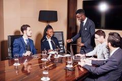 Афро-американский бизнесмен давая представление к сподвижницам Стоковое фото RF