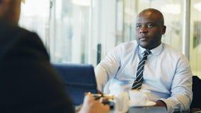 Афро-американский бизнесмен жестикулируя и объясняя его детали запуска к инвестору в официально носке в стекловидном кафе видеоматериал
