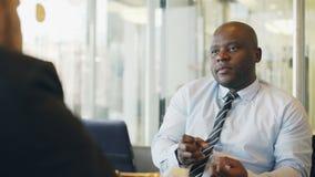Афро-американский бизнесмен жестикулируя и объясняя его детали запуска к инвестору в официально носке в стекловидном кафе сток-видео