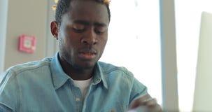 Афро-американский бизнесмен пишет примечания смотря монитор ноутбука работая в офисе видеоматериал