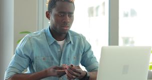 Афро-американский бизнесмен пишет примечания смотря монитор ноутбука работая в офисе сток-видео