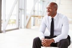 Афро-американский бизнесмен смотря прочь, горизонтальный стоковое изображение