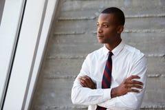 Афро-американский бизнесмен стоя против стены стоковые фото