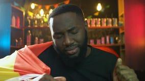 Афро-американский вентилятор со спичкой испанского флага наблюдая в пабе, осадил о поражении сток-видео