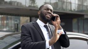 Афро-американский дипломат обсуждая телефоном, защищающ его интересы и мнение стоковое изображение rf