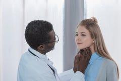Афро-американский доктор ощупывая женская терпеливая лимфа стоковая фотография rf