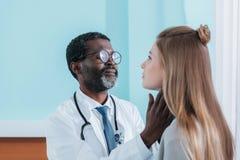 Афро-американский доктор ощупывая терпеливая лимфа стоковые фото
